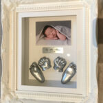 3d hand and foot casts in vintage frame with letter